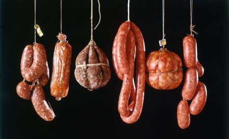embutidos: Surtido de diferentes tipos de salchichas italianas picantes frescos salir para curar y secar en una carnicer�a contra un fondo negro Foto de archivo