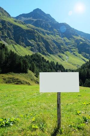 Letrero blanco en blanco en un valle de monta�a exuberante de pie al borde de un campo verde en un d�a soleado de verano Foto de archivo