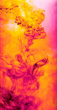 Colourful abstract background of swirling orange and pink ink in water creating sinuous tendrils in a random pattern photo