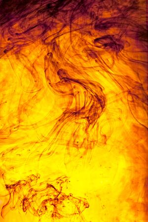 sinuous: Swirling colourful tendrils of orange ink dispersing in water creating an abstract fluid sinuous pattern
