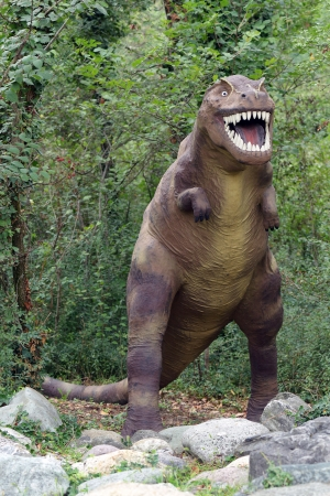 bipedal: Tyrannosaurid dinosaur, an extinct prehistoric carnivorous predator with reduced forelimbs and strong powerful legs with bipedal movement baring its fearsome teeth, model reconstruction in a park Stock Photo