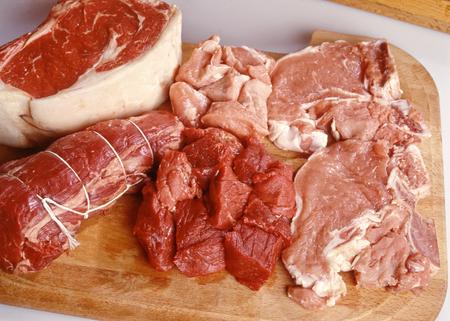 carnes rojas: Surtido de embutidos sin cocer crudos de carne roja muestran en una tabla de madera con carne de res y cerdo, gran angular