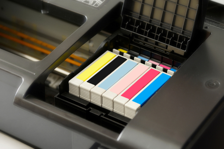 consumable: Row of individual ink cartridges in an office printer in CMYK colour palette