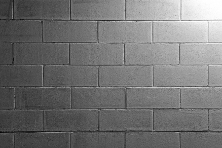 sidelit: Background texture of a white brick or cement block wall in a commercial building lit from the top right corner graduating into shadow