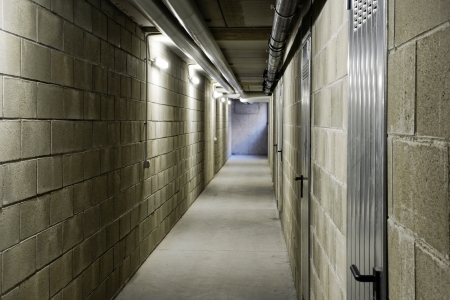 bloc: Long empty internal passageway or corridor with wall lighting and a cement block construction