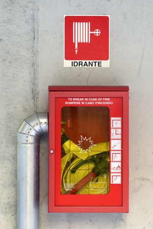 Emergency fire hose inside a glass fronted box mounted on a wall attached to a metal hydrant to provide water flow and pressure in an emergency photo