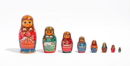 smallest: Close-up of a set of Russian decorative Matryoshka dolls, in a row, in order of size, from the biggest to the smallest one, on light grey background, with copy space Stock Photo