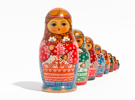 Close-up of traditional Russian matryoshka dolls, placed one behind the other in the order of size, from the biggest to the smallest, on light grey background photo