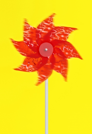 revolves: Colourful red pinwheel a childs toy with plastic vanes pinned to a stick that revolves in the wind like a windmill Stock Photo