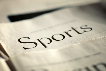 Edition of the daily newspaper with selective focus to the header in the Sports section lying flat on a table, low angle Banque d'images
