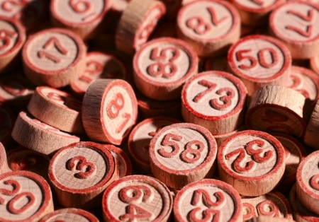 Background of lucky bingo numbers on round wooden tokens to be drawn at random during the game and marked off on the bingo cards for a win