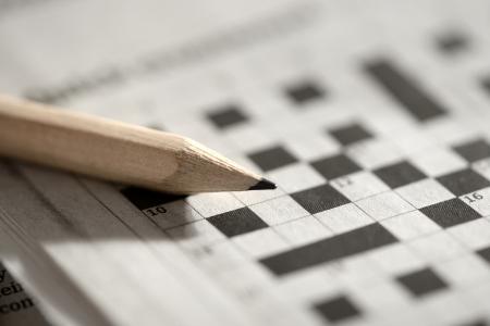검은 색과 흰색 사각형과 연필로 빈 크로스 워드 퍼즐 그리드의 얕은 DOF와보기를 닫습니다 스톡 콘텐츠