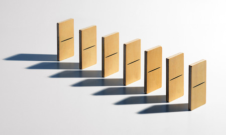 upright row: Set of blank wooden dominoes standing upright in a receding oblique row casting a forward shadow