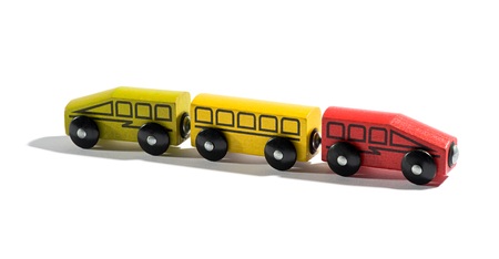 either: Colourful hand crafted wooden toy train with an engine at either end in red and yellow on a white