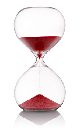 Hourglass with red sand running through the clear glass bulbs measuring the passing time in a countdown to the finish standing at the half way position on a white background