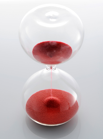 High angle close up view of a clear glass hourglass with red sand running through the bulbs marking the passing of the time and counting down to the end, on light grey photo