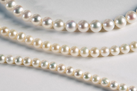 diameters: Three different strands of stylish cultured pearls with different coloured nacre and differing bead diameters on a light grey background