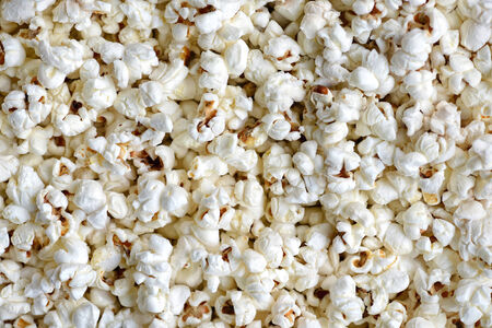 popped: Background texture of freshly made popcorn with irregularly shaped white puffs of popped corn for a delicious snack, conceptual of the cinema