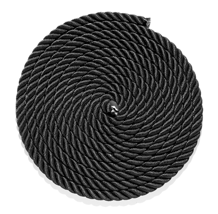 coiled rope: Overhead view of a neatly coiled braided plaited black rope with intertwined fibres giving a spiral pattern and texture isolated on white Stock Photo