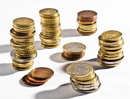 Las pilas de monedas de euro en las diferentes denominaciones dispuestas sobre un fondo blanco en un concepto financiero Foto de archivo