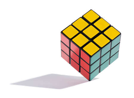 Colourful solved Rubiks Cube balanced on edge, a puzzle game requiring all the squares of a particular colour be arranged on each side of the cube, on a white background with a shadow Stock Photo