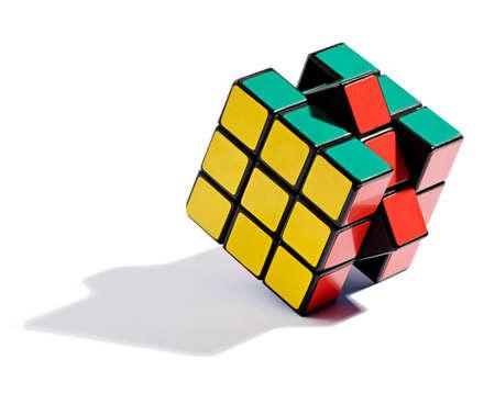 Resolver el rompecabezas del cubo de Rubik con los cuadrados de colores finales que se mueve en su lugar, de pie en el borde sobre un fondo blanco arroja sombras