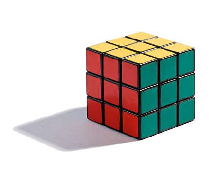 Resuelto rompecabezas Cubo de Rubiks en blanco con cada color en su parte asignada del cubo en un juego de habilidad e inteligencia, con una sombra y copyspace