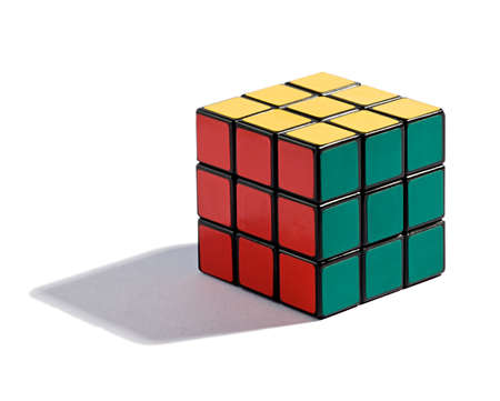 scramble: Solved Rubiks Cube puzzle on white with each colour on its allotted side of the cube in a game of skill and intelligence, with a shadow and copyspace Stock Photo