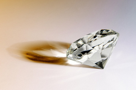 Faceted gemstone or diamond lying on its side on a white background casting an interesting shadow Stock Photo