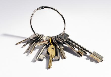 Gran manojo de llaves mixtas, incluyendo una clave larga de seguridad en un anillo de metal simple en un fondo blanco Foto de archivo
