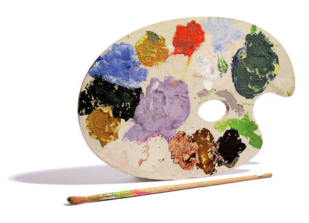 daubed: Artists palette with colorful daubs of different coloured paints standing upright with an old used paintbrush in the foreground on a white background Stock Photo