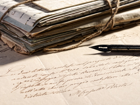 correspondencia: Escribir un concepto escrito con una pluma retro estilográfica acostado en una vieja carta se desvaneció y una pila de vendimia viejo y gastado correspondencia atado con una cuerda Foto de archivo