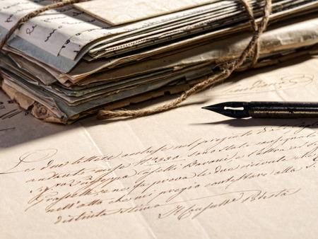 PAPIER A LETTRE: Rédaction d'un concept de lettre avec un stylo plume rétro couché sur un vieille lettre fanée et une pile de correspondance vieilli et usé cru ficelé