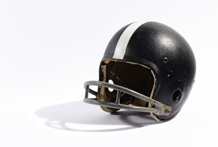 face guard: Old black football helmet with a metal face protection guard and white decorative stripe on a white background