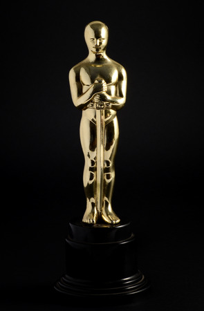 Golden replica of an Oscar film award on a black background