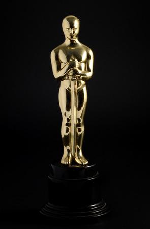 Golden replica of an Oscar film award on a black background