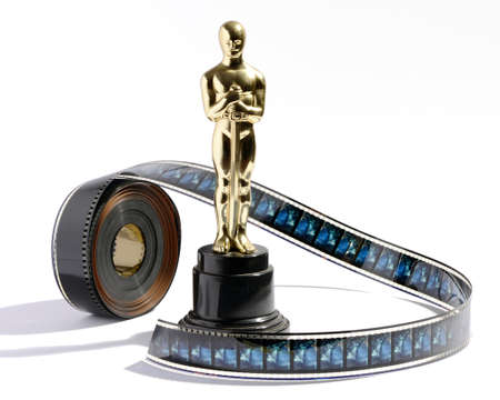 replica: Replica golden Oscar statue on a black plinth standing on a white background with a roll of movie film