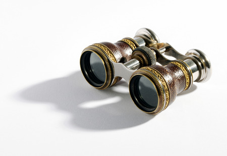 Pair of small vintage binoculars or opera glasses with a metal frame for magnifying objects at a distance on a white background with shadow detail