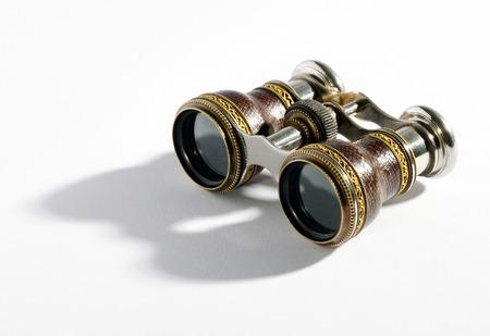 Par de binoculares antiguos peque�os o anteojos de �pera con un marco de metal para magnificar objetos a una distancia sobre un fondo blanco con detalles en las sombras Foto de archivo
