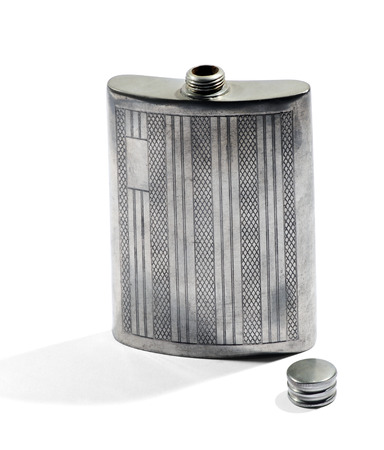 concave: Classic concave curved silver metal hip flask for carrying whiskey in a pocket of ones clothing with engraved patterns on the front and the lid removed isolated on white Stock Photo