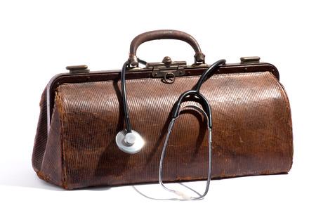 Oude bruine lederen dokterstas met een stethoscoop lus rond het handvat in een medische en gezondheidszorgconcept, op een witte achtergrond