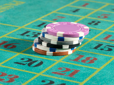 Stack of casino chips or tokens on a numbered roulette board in payment of a bet in a gambling game of luck and chance
