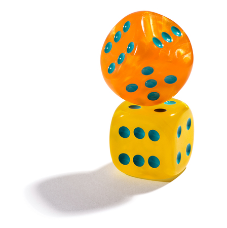 yelllow: Two colorful yelllow and orange dice balancing on each other with the top one angled on a white background conceptual of gambling, betting and a casino Stock Photo