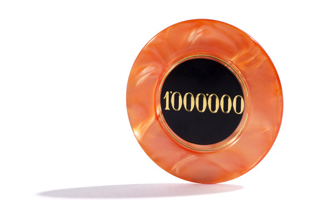 high stakes: One million casino chip for a bet in a high stakes gambling game standing upright on a white background with copyspace and shadow