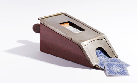 dispensing: Vintage metal card dispenser for dispensing playing cards during a card game such as poker on a white background Stock Photo