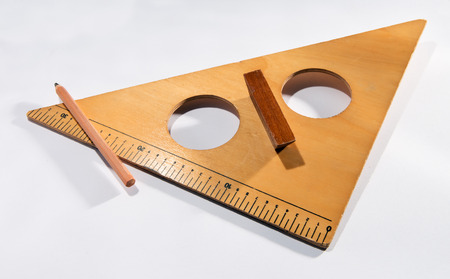 obtain: Vintage wooden set square in the form of a triangle with two round holes used for technical and engineering drawings to obtain a perfect right angle