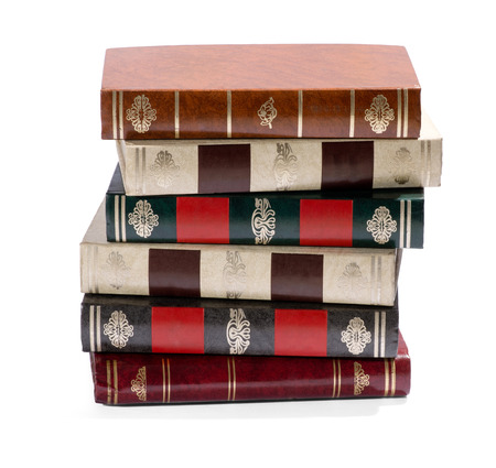 tooled: Stack of untitled old books with decorative gilt tooled spines facing the camera, isolated on white