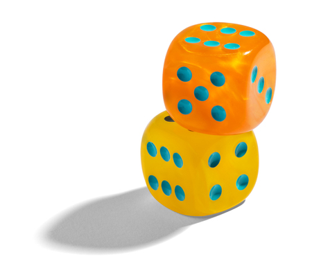 Yellow and orange dice stacked on on top of the other on a white used to generate random numbers in tabletop games such as craps or in a casino , with copyspace photo