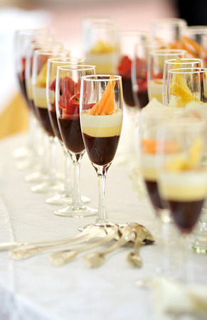catered: Tall elegant glasses of assorted chocolate cream desserts topped with fresh fruit displayed on a buffet table at a catered event or reception