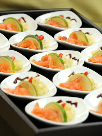 catered: Individual dishes of gourmet smoked salmon appetizers served with tangy fresh lemon displayed on a tray on a buffet table at a catered event for a delicious seafood starter